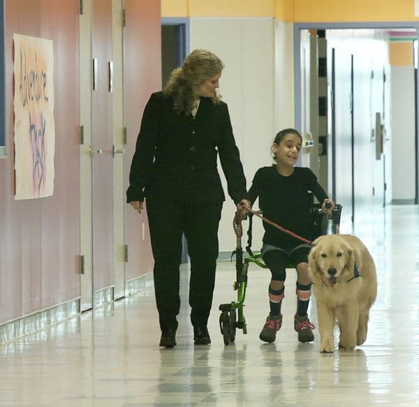 Kim Pruitt walking the school halls with a student and Josie